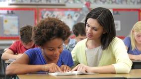 Nauczyciela czytanie Z Żeńskim uczniem W klasie zbiory wideo