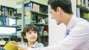 nauczyciela i chłopiec uczeń uczy się z książką z półka na książki backgroun zdjęcie royalty free