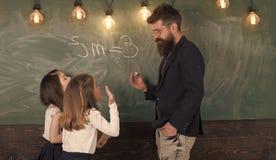 Nauczyciela i dziewczyn ucznie w sala lekcyjnej blisko chalkboard Mężczyzna z brodą w formalnym kostiumu uczy uczennicom physics zdjęcia royalty free