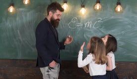 Nauczyciela i dziewczyn ucznie w sala lekcyjnej blisko chalkboard Mężczyzna z brodą w formalnym kostiumu uczy uczennicom physics zdjęcia stock
