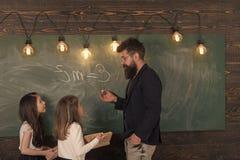 Nauczyciela i dziewczyn ucznie w sala lekcyjnej blisko chalkboard Mężczyzna z brodą w formalnym kostiumu uczy uczennicom physics obrazy royalty free