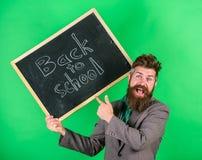 Nauczyciela mężczyzna chwytów brodaty blackboard z inskrypcją z powrotem szkoły zieleni tło Zaprasza świętować dzień fotografia royalty free