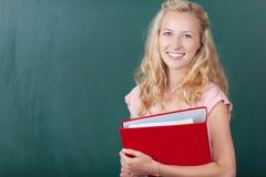 Nauczyciela mienia segregator Przeciw Chalkboard Fotografia Stock