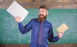 Nauczyciela modnisia brodaci chwyty książka i laptop Co ty wolał Nauczyciel wybiera nowożytnego nauczania podejście Papier zdjęcie royalty free