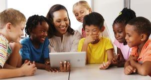 Nauczyciela nauczania szkoły dzieciaki na cyfrowej pastylce w sala lekcyjnej zbiory wideo