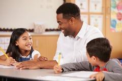 Nauczyciela obsiadanie przy biurkiem z dwa szkoła podstawowa uczniami obraz royalty free