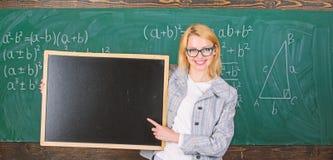 Nauczyciela przedstawienia szko?y informacja Nauczyciel kobiety chwyta m?drze u?miechni?tego blackboard reklamy kopii pusta przes obraz stock