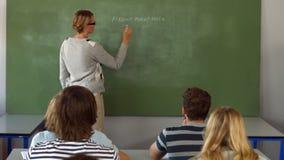 Nauczyciela writing na blackboard w klasie zbiory
