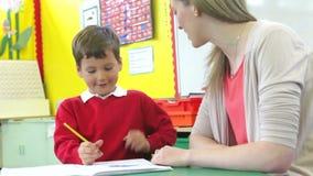 Nauczyciela Writing Z Męskim uczniem Przy biurkiem zdjęcie wideo