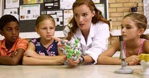 Nauczyciela wyjaśniać dzieciaki o cząsteczkowym modelu w laboratorium zbiory