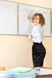 Nauczycieli stojaki przy writing w sala lekcyjnej i blackboard Zdjęcia Stock