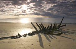 Naufragio en la playa en la puesta del sol imagen de archivo