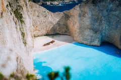Naufragio famoso sulla spiaggia di Navagio con l'acqua di mare del blu di turchese circondata dalle scogliere bianche enormi Limi immagine stock