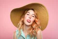 Naughtiness antics frolicking girl sunhat tongue. Female naughtiness. cute antics and frolicking concept. mischievous childish behavior. portrait of a young stock images