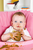 Naughty baby girl making a mess while eating Royalty Free Stock Photography