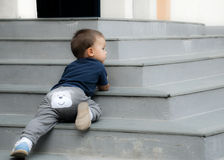 Naughty baby. Lying on the stairs outdoor Royalty Free Stock Photo