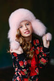 Naughty blond girl in a bright pink sweater and a fur hat smilin Stock Photography