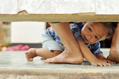 Naughty boy. Asian thai boy play under the bench Stock Photo