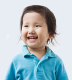 Naughty boy. A cute little Asian boy, isolated on white, grey Royalty Free Stock Photos