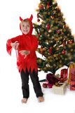 Naughty boy in devil costume near Christmas tree Royalty Free Stock Images
