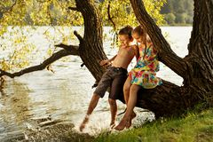 Naughty boy and girl sitting on a branch over water, laughing, having fun talking Royalty Free Stock Photography