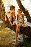 Naughty boy and girl sitting on a branch over water, laughing out loud, having fun talking Stock Photo