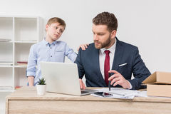 Naughty boy with his father businessman Stock Image