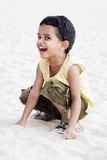 Naughty boy laughing. Little boy laughing while playing at the beach Royalty Free Stock Photography