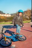 Naughty boy screaming and kicking his bike on Stock Photography