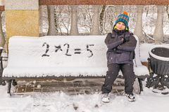 Naughty boy wrongly decides an example on a snow-covered bench Stock Image