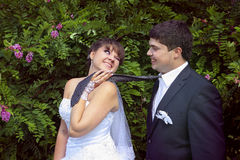 Naughty bride leads her groom on a tie and winks royalty free stock images