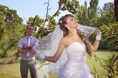 Naughty bride and loving groom fooling around. On a bank of river Royalty Free Stock Photos