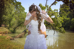 Naughty bride and loving groom fooling around. On a bank of river Royalty Free Stock Photo