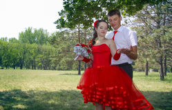 Naughty bride in red dress and her groom Royalty Free Stock Photos