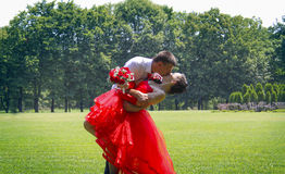Naughty bride in red dress and her groom Royalty Free Stock Photo