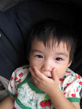 Naughty child covering mouth. Asian toddler sitting in stroller covering her mouth in mischief Royalty Free Stock Photo