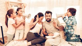 Naughty Children Annoying Parents Reading Books. Naughty Children Annoying Parents. Kids Playing with Speaker. Three Kids Having Fun while Dad and Mom Having royalty free stock images