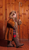 Naughty cowgirl in my mother's fur coat, boots and a staff. Farm. Royalty Free Stock Photo