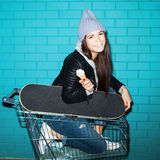 Naughty girl eating ice cream. Young funky hipster woman nose smeared in shopping cart over blue brick wall. Naughty girl having fun . Indoors, lifestyle Royalty Free Stock Photos