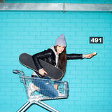 Naughty girl eating ice cream. Young funky hipster woman with ice cream and skateboard sitting in shopping cart over blue brick wall. Naughty girl having fun Royalty Free Stock Image