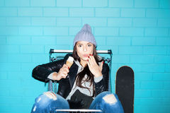 Naughty girl eating ice cream. Young hooligan hipster woman eating ice cream over blue brick wall. Naughty girl having fun in shopping cart. Indoors, lifestyle Royalty Free Stock Image