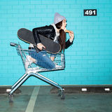 Naughty girl eating ice cream. Young trendy woman with skateboard eating ice cream in shopping cart over blue brick wall. Naughty girl having fun . Indoors Royalty Free Stock Photography