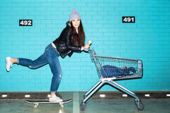 Naughty girl having fun. Young funky hipster woman riding skateboard in front pushing shopping cart over blue brick wall. Naughty girl having fun . Indoors Stock Photo