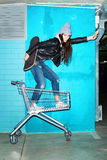 Naughty girl having fun. Young funky hipster woman standing with ice cream and skateboard in shopping cart over blue brick wall. Naughty girl having fun Royalty Free Stock Photography