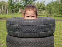Naughty girl peeps out of the tires Stock Images