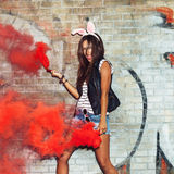 Naughty girl in pink rabbit ears with red smoke bombs Royalty Free Stock Photo