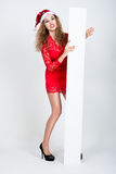 Naughty girl in red dress and santa hat with blank white banners Royalty Free Stock Image