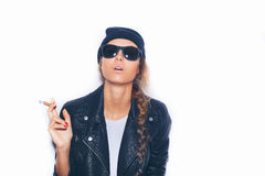Naughty girl in sunglasses and black leather jacket smoking cigar Stock Image