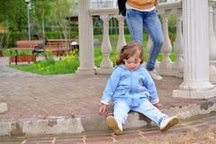 Naughty Girl 2 years old sitting on ground Stock Photo