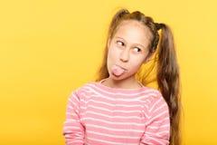 Naughty girl sticking tongue frolicking childish. Naughty girl on yellow background sticking her tongue out. frolicking and childish behavior stock image